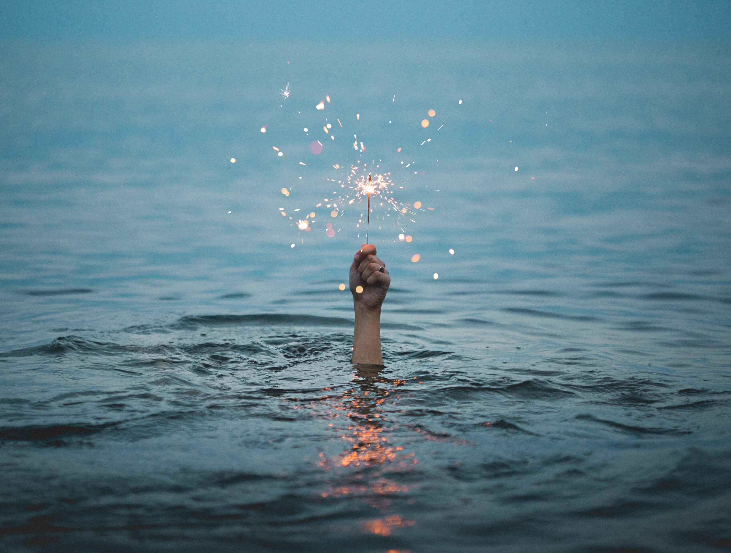 A hand holding a lit sparkler rises from a pool of water.